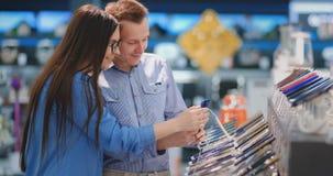 El par elige un teléfono móvil en una tienda electrónica Escaparate con smartphones almacen de video