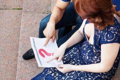 El par embarazada planea una fecha de nacimiento del bebé con el calendario imagen de archivo libre de regalías