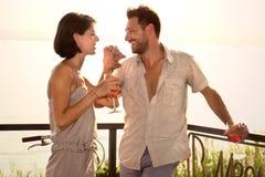 El par en amor bromea en el spritztime en la orilla del lago fotografía de archivo libre de regalías