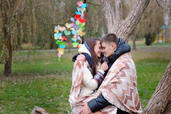 El par en amor debajo de la manta es parque heated del otoño Foto de archivo libre de regalías