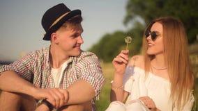 El par en blowballs que soplan del amor florece en caras de uno a Gente sonriente y de risa que tiene buen tiempo afuera el veran