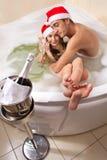 El par en los sombreros de santa está disfrutando de un baño Imagenes de archivo