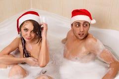 El par en los sombreros de santa está disfrutando de un baño Foto de archivo libre de regalías