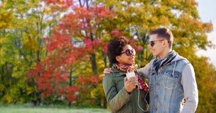 El par escucha música por smartphone en parque del otoño imagen de archivo libre de regalías