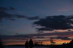 El par está caminando a lo largo de la playa durante puesta del sol fotos de archivo