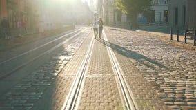 El par está caminando a lo largo del tranvía metrajes