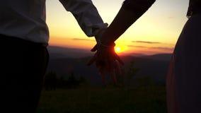 El par está dando la mano el uno al otro en el fondo del cielo colorido durante la puesta del sol Opinión del primer del almacen de video