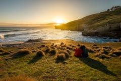 El par está disfrutando de puesta del sol hermosa en la playa del túnel de Nueva Zelanda imagenes de archivo