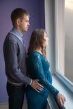 El par está mirando hacia fuera la ventana fotografía de archivo libre de regalías