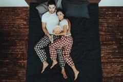 El par está mirando el vídeo y está comiendo las palomitas en cama imagen de archivo
