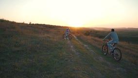 El par está montando una bicicleta en la puesta del sol almacen de video