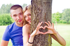 El par está poniendo sus manos en árbol en una forma del corazón Fotos de archivo