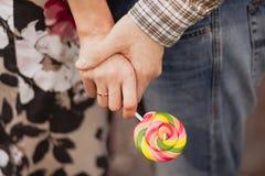 El par está sosteniendo las manos y el caramelo Imágenes de archivo libres de regalías