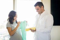 El par expectante que elige al bebé viste en casa fotos de archivo
