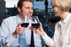 El par feliz aumenta un vidrio de vino rojo fotos de archivo