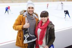 El par feliz con patina sobre hielo en pista de patinaje Foto de archivo libre de regalías