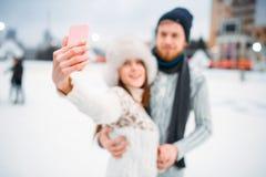 El par feliz del amor hace el selfie en pista de patinaje Fotografía de archivo