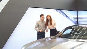 El par feliz elige el primer coche familiar para comprar en una sala de exposición almacen de video