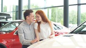 El par feliz elige el primer coche familiar para comprar en una sala de exposición metrajes