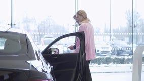 El par feliz elige un nuevo vehículo en una concesión de coche Sala de exposición del coche metrajes