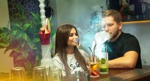 El par feliz fuma los cócteles del shisha y de la bebida Fotografía de archivo