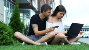 El par feliz hace compras en línea usando el ordenador portátil, elige mercancías e incorpora un número de tarjeta de crédito que almacen de video