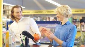 El par feliz joven pone productos numerosos en la caja registradora para el pago almacen de metraje de vídeo