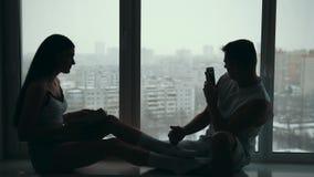 El par feliz joven que se sienta en el alféizar, muchacha que lee un libro y a un individuo sonriente está tomando las imágenes d almacen de video
