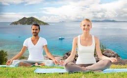El par feliz que hace yoga ejercita al aire libre Foto de archivo libre de regalías