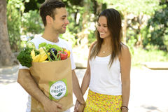 El par feliz que lleva una bolsa de papel del reciclaje de la American National Standard orgánica de las verduras da fruto por com Imagenes de archivo