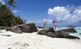 El par feliz que se coloca en el granito oscila en Seychelles Fotos de archivo