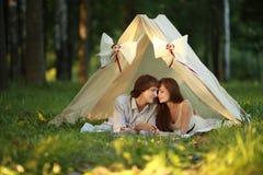 El par feliz se está besando en la tienda en la tarde del verano Imágenes de archivo libres de regalías
