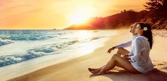 El par feliz se sienta en la costa del océano foto de archivo