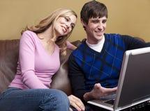 El par feliz sonríe en el ordenador Imagenes de archivo