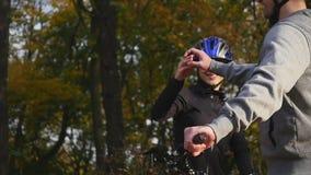 El par feliz va en una carretera de asfalto de la montaña en el bosque en las bicis con los cascos que se dan altos cinco almacen de metraje de vídeo