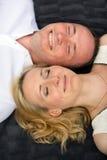 El par feliz y sonriente con los ojos cerrados miente en una tela escocesa gris Foto de archivo libre de regalías