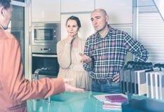 El par hace demandas en el taller de los muebles de la cocina foto de archivo