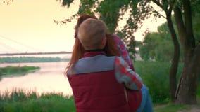 El par hermoso, colgando junto, individuo levanta su novia en el aire y las vueltas, la atmósfera del amor y el cuidado almacen de video