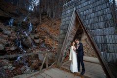 El par hermoso de la boda abraza en el puente de madera en montañas Fondo de la cascada Imágenes de archivo libres de regalías