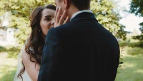 El par hermoso de la boda en abrazo, mira y se acaricia metrajes