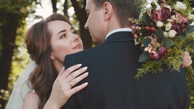 El par hermoso de la boda en abrazo, mira y se acaricia almacen de video