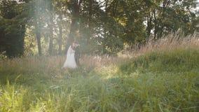 El par hermoso de la boda en abrazo, mira y se acaricia almacen de metraje de vídeo