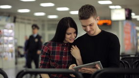El par hermoso de la gente se sienta en salón de la salida en aeropuerto almacen de video