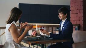 El par hermoso está teniendo fecha romántica en restaurante cuando el hombre joven está haciendo oferta a la mujer feliz que da s almacen de metraje de vídeo