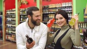 El par hermoso est? sonriendo mientras que elige la bebida alcoh?lica en el supermercado almacen de video