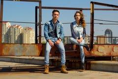 El par hermoso joven de la moda que lleva vaqueros viste en luz del día Imagen de archivo