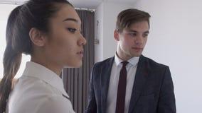 El par hermoso joven del negocio está hablando, colocándose en el espacio de oficina, colaborando en proyecto, tiene diálogo sobr almacen de metraje de vídeo