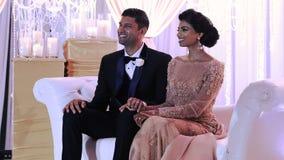El par indio elegante vestido para un evento de la tarde se sienta en el sofá rosado almacen de video