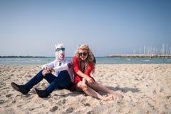 El par inusual se sienta en la playa en el fondo del mar y del cielo Imagen de archivo