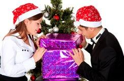 El par joven abre un regalo en el partido del Año Nuevo Foto de archivo